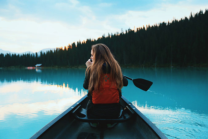 blonde woman boating on lake