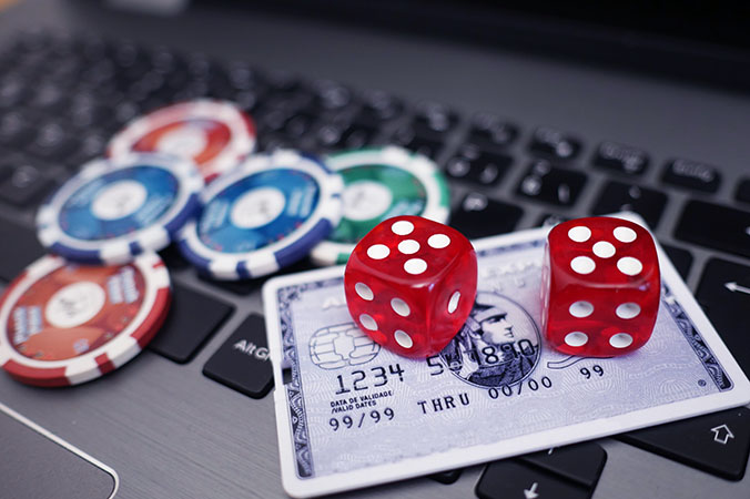 dice and casino chips on laptop keyboard
