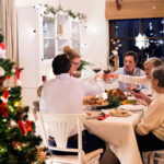 family sitting at the table, celebrating Christmas together at home