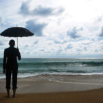 person with umbrella on the beach
